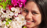 young woman in flowers smiling happy