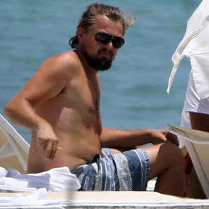 Exclusive... 51481469 'Wolf Of Wall Street' actor Leonardo DiCaprio relaxes beachside in Miami, Florida on July 19, 2014. Leo is spotted removing his t-shirt and exposing his un-toned stomach while smoking a cigarette. FameFlynet, Inc - Beverly Hills, CA, USA - +1 (818) 307-4813
