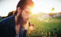 hipster guy man with beard and pipe sunset