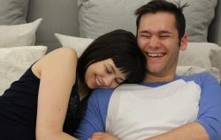 couple bed happy laughing