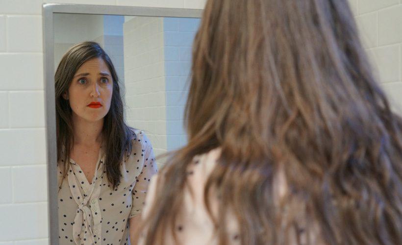 woman mirror bathroom sad