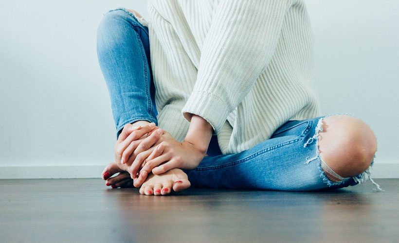 jeans woman sitting sweater barefoot pedicure