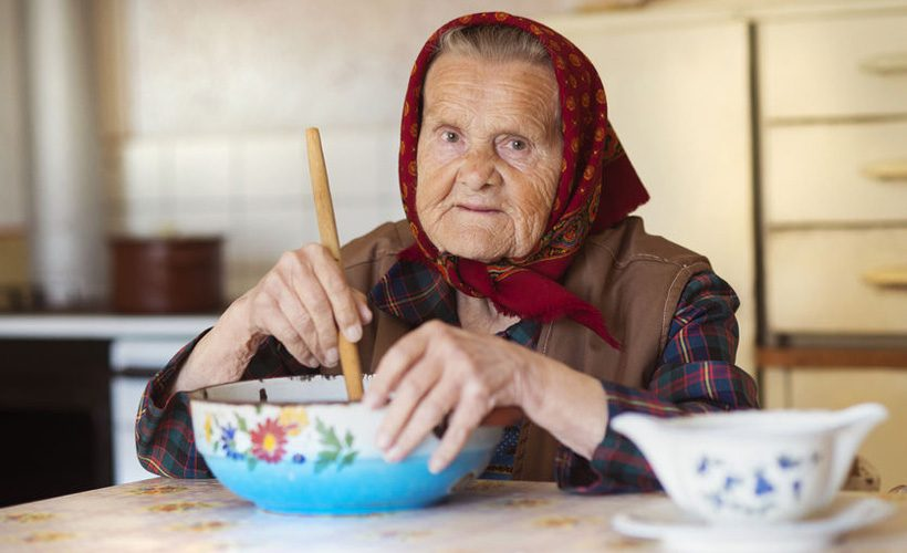 very old woman preparing food in her old country style kitchen
