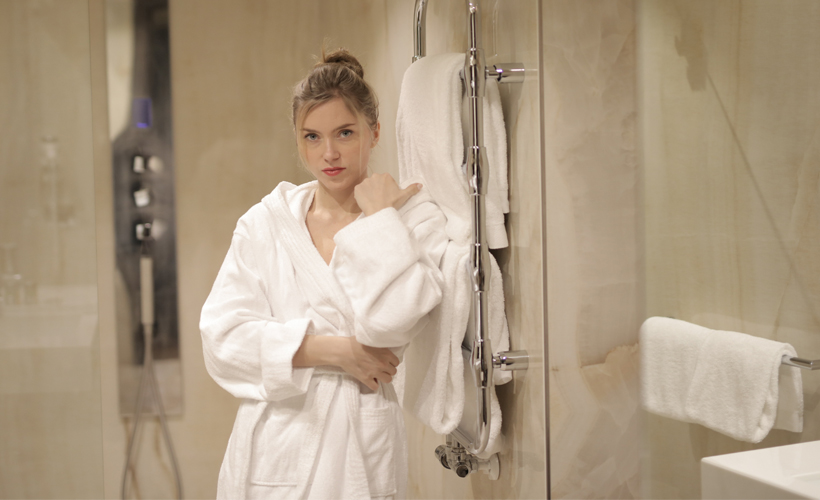 women in bathrobe outside shower