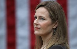 amy coney barrett in front of an american flag