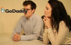 woman listening in meeting, go daddy logo in corner
