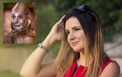woman smiling with pic of tin man in corner