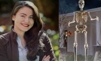 woman proud next to 12 foot home depot skeleton