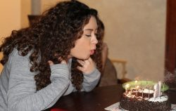 woman blowing out birthday candles